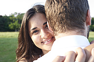 Portrait of happy young woman hugging her partner - IGGF00045
