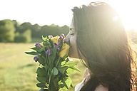 Profile of young woman smelling  bunch of flower at sunset - IGGF00054