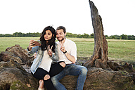 Young couple in nature taking selfie with smartphone pulling funny faces - IGGF00057