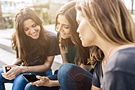 Three happy young women sitting outdoors looking at cell phone - GIOF02987