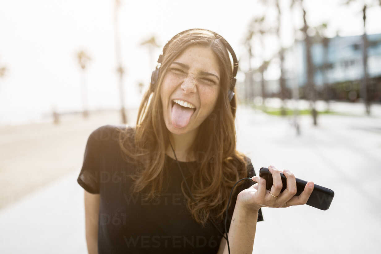 Carefree young woman on boardwalk listening to music - GIOF02990 - Giorgio Fochesato/Westend61