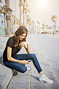 Smiling young woman sitting on steps listening to music - GIOF02993
