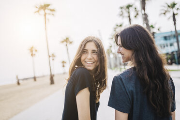 Two happy young women on boardwalk - GIOF02999