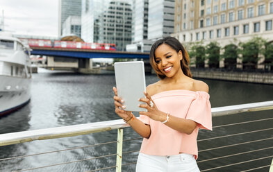 Smiling woman taking a selfie with her tablet in the city - MGOF03456