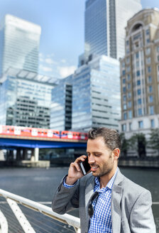 Businessman talking on the phone in the city - MGOF03471