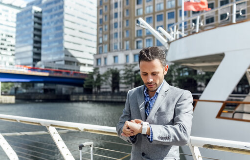 Businessman checking the time in the city - MGOF03474