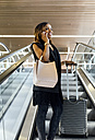 Smiling woman talking on the phone on escalator - MGOF03477