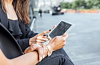 Close-up of two women using a tablet in the city - MGOF03480