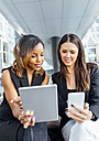 Two businesswomen working with smartphone and tablet in the city - MGOF03483