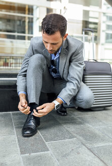 Businessman tying his shoes in the city - MGOF03492