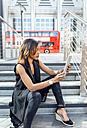 Woman using a tablet in the city - MGOF03504