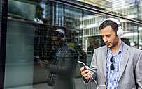 Businessman listening to music with headphones in the city - MGOF03513