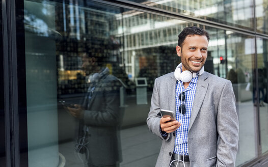 Smiling businessman with headphones and cell phone in the city - MGOF03516