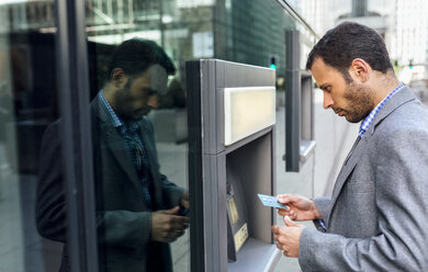 Businessman taking money at an ATM in the city - MGOF03519