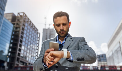 Businessman synchronizing his devices in the city - MGOF03522