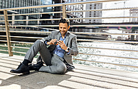 Businessman sitting on a bridge with cell phone in the city - MGOF03525