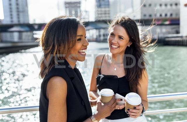 Two happy women having a coffee break on a bridge in the city - MGOF03528