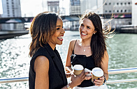 Two happy women having a coffee break on a bridge in the city - MGOF03528