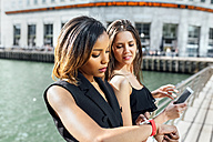 Two women on a bridge with cell phone and smartwatch - MGOF03534