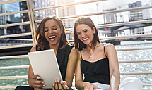 Two happy women sitting on a bridge sharing a tablet in the city - MGOF03537