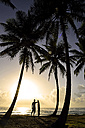Dominican Rebublic, silhouette of palms and man with surfboard at sunset - ECPF00006