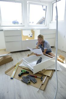 Woman reading assembly instructions at home - ECPF00011
