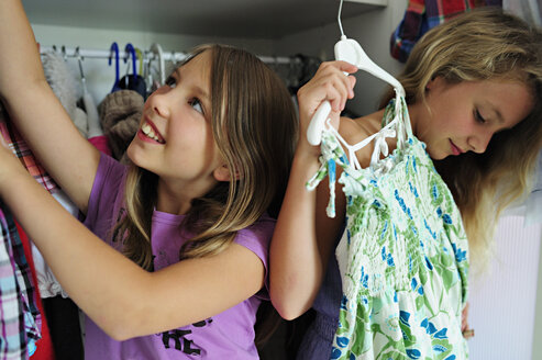 Two girls choosing clothes from wardrobe - ECPF00017