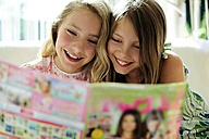 Two girls reading teen magazine - ECPF00029