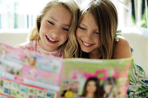 Two girls reading teen magazine - ECPF00029