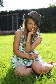 Smiling girl wearing hat sitting in garden - ECPF00038