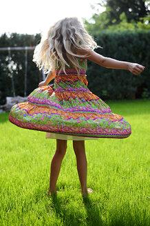 Girl wearing a dress turning in garden - ECPF00041