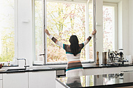 Woman in kitchen opening the window - JOSF01242