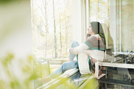 Woman in kitchen looking out of window - JOSF01245