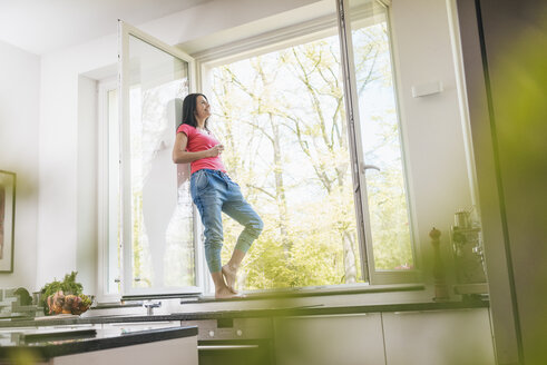Smiling woman standing in kitchen on windowsill - JOSF01248