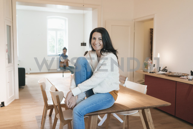 Portrait of smiling woman sitting on table at home - JOSF01251 - Joseffson/Westend61