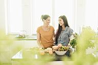 Two smiling women in kitchen preparing fruit - JOSF01254