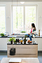 Woman in kitchen looking out of window - JOSF01263