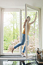 Happy woman standing on windowsill cleaning the window - JOSF01266