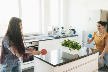Two women playing table tennis on kitchen counter - JOSF01269