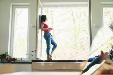 Woman standing in kitchen on windowsill - JOSF01272