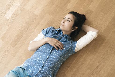 Woman lying on wooden floor - JOSF01296
