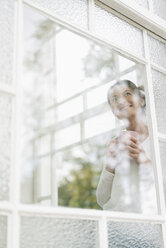 Smiling woman with cup of coffee looking out of window - JOSF01308