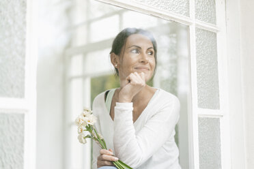 Smiling woman with flowers out of window - JOSF01311