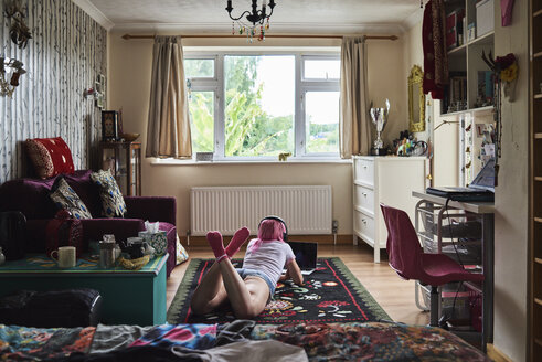 Young woman with pink hair lying on carpet wearing headphones and using laptop at home - IGGF00061