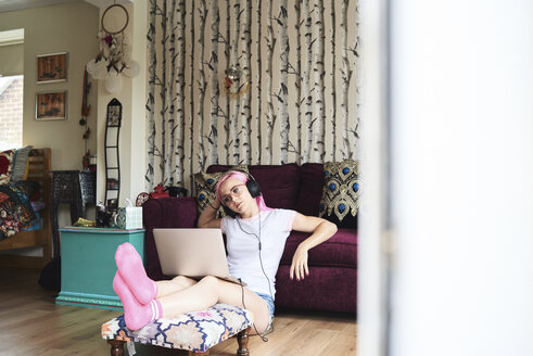 Young woman with pink hair wearing headphones and using laptop at home - IGGF00064