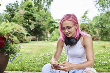Young woman with pink hair wearing headphones and using cell phone in garden - IGGF00073