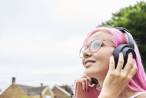 Young woman with pink hair listening to music outdoors - IGGF00076