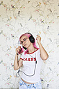 Enthusiastic young woman with pink hair listening to music at home - IGGF00079