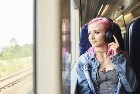 Young woman with pink hair listening to music while traveling by train - IGGF00082