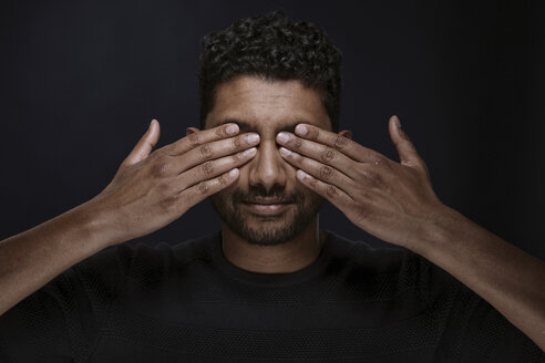 Portrait of man covering eyes with his hands - PRAF00042